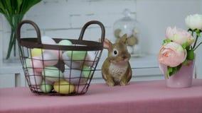 Målade ägg i en korg och en påskkanin