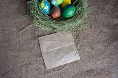 Målade ägg i ett rede av hö Arkivfoto
