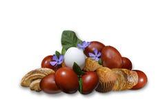 Målade ägg med söta bakelser och den delikata blommavintergrönan Arkivbilder