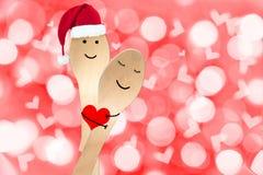 Målade det lyckliga parbegreppet för jul, smiley på skedar, röd bakgrund för ferie med suddiga ljus Royaltyfri Foto