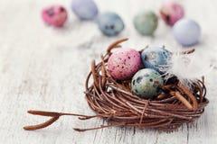 Målade easter ägg i rede på lantlig träbakgrund, tappningstil Royaltyfri Foto