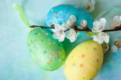 Målade easter ägg och filialer av den vårsakura closeupen på ett ljus - blå bakgrund med utrymme för lyckönskan Royaltyfria Bilder