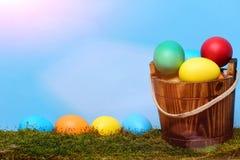 Målade easter färgrika ägg i trähink med grön mossa Arkivfoto