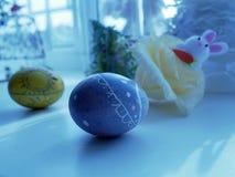 Målade fega ägg, påskleksakkaniner, dekor på fönsterbrädan arkivbild