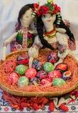 Målade påskägg i korgen med traditionella dockor Royaltyfri Bild