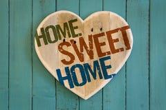 Målade trähjärta för det hem- sötsakhemmeddelandet på turkos backgr fotografering för bildbyråer