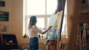 Målar den unga damen för den yrkesmässiga målaren seascape med akrylmålarfärger som visar marin- landskapskepp- och havsvågor stock video