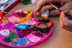 målar palettvattenfärg Hand med paintbrushen royaltyfri fotografi
