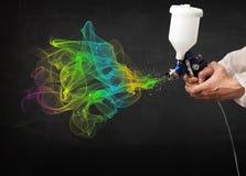 Målare som arbetar med retuschsprutan och färgrik målarfärg för målarfärger Arkivfoton