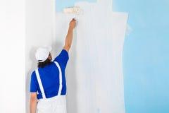 Målare som målar en vägg med målarfärgrullen arkivfoton