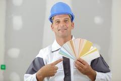 Målare som pekar på färger för att måla jobb royaltyfri bild