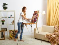 Målarekvinnlig med träsketchbook- och målningståenden royaltyfri foto