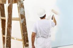 Målareman på arbete med en målarfärgrulle, väggmålning arkivbild