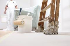 Målareman på arbete med en rulle, en hink och en stege royaltyfria bilder