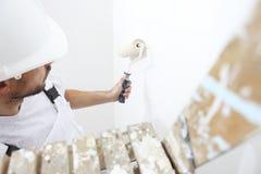 Målareman på arbete med målarfärgrullen, på stege, väggpaintin arkivfoto