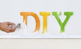 Målaremanhand med text för målning för målarfärgborste som är diy på den vita boaen royaltyfria foton