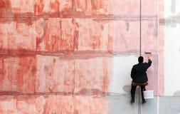 Målaren arbetar på den yttre byggnadsväggen Royaltyfri Bild