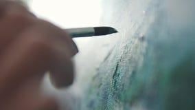 Målaren gör en borsteslaglängd på bilden closeupmålarfärgborste arkivfilmer