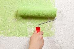 Målaren målar en vägg med en målarfärgrulle Arkivbild