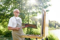 Målaren som står på, parkerar och upp väljer målarfärg för att föreställa royaltyfri foto