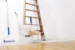 Målareväggbegrepp, stege, hink, rullmålarfärg på golvet royaltyfria foton
