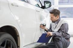 Målarfärg för bilen för den manliga reparationsarbetaren shoppar undersökande med utrustning i reparation arkivbild