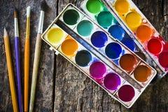 Målarfärg för två vattenfärg och blyertspenna, olik fanborste som ska målas på ett gammalt trä Arkivbild