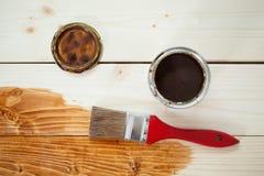Målarfärg kan och målarpenseln på träplankor Royaltyfria Bilder