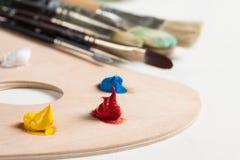 Målarfärg och målarfärgborstar på pallette arkivfoton