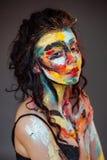 Målarfärg på framsidan av en ung flicka Arkivbild