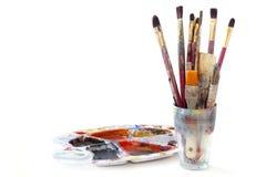 Målarfärgborstar i ett exponeringsglas och en använd pallete med färger som isoleras Royaltyfri Foto