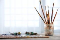 Målarfärgborstar med en palett Arkivfoton