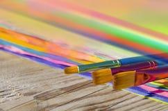 Målarfärgborstar och färgat papper på träbakgrund Royaltyfria Foton