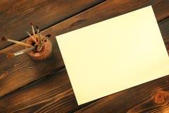 Målarfärgborstar och papper på träbakgrund royaltyfri illustrationer