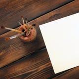 Målarfärgborstar och papper på träbakgrund royaltyfria bilder