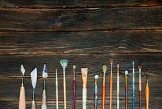 Målarfärgborstar på en mörk träbakgrund, bästa sikt Begrepp av Fotografering för Bildbyråer