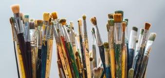 Målarfärgborstar på en suddighetsbakgrund och konstnär rymmer borsten Arkivfoto
