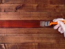 Målarfärgborste på en trätabell Husrenovering Lacka naturligt trä med ett sudd av målarfärgborsten arkivbilder