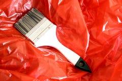 Målarfärgborste på röd folie Arkivbilder