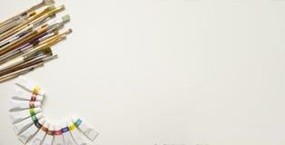 Målarfärger och borstar, på en vit bakgrund arkivbild