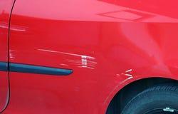 Målarfärgskrapor på en röd bil Tillfällig skada till en röd bil arkivfoto