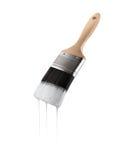 Målarpensel som laddas med vit färg som dryper av borsten Arkivfoto