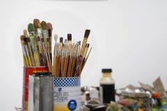 Målarpenslar i en kruka eller en krus på galleristudion Arkivbild