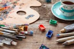 Målarpenslar, konstnärpalett, blyertspennor, kaffekopp och målarfärger Arkivfoton