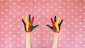 Målat färgrikt räcker idérikt konst Hand i färgmålarfärg smutsigt gömma i handflatan Rosa bakgrund stock video