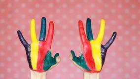 Målat färgrikt räcker idérikt konst Hand i färgmålarfärg smutsigt gömma i handflatan Rosa bakgrund lager videofilmer
