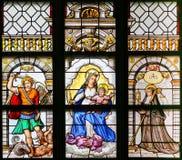 Målat glass - ärkeängel Michael, Madonna och barn och helgon T arkivfoto