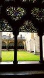 Målat glassfönster av den forntida kyrkan som förbiser grönt gräs av borggården Royaltyfria Foton