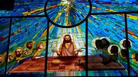 Målat glassfönster som visar Jesus och arkivfoto