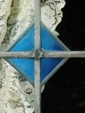 Målat glassfönstret med snör åt gardinblått Arkivbilder